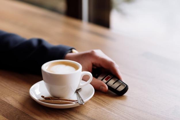 Zamknij widok kluczyków do samochodu postawionych na stole obok filiżanki kawy przez bogatego biznesmena w kawiarni. przerwa na kawę w kawiarni lub restauracji.