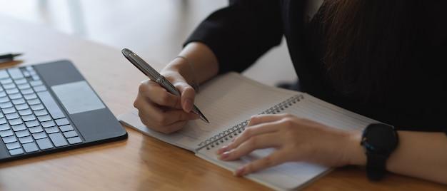 Zamknij widok kobiecej dłoni pisania w książce harmonogramu na biurko z materiałów biurowych