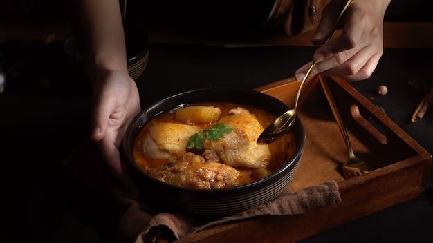 Zamknij widok kobiecej dłoni trzymającej drewnianą tacę z miską kurczaka