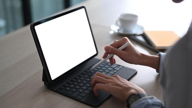 Zamknij widok kobiety ręki trzymającej rysik i pracy na tablecie komputerowym przy biurku.