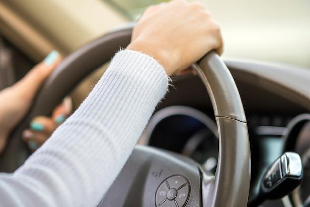 Zamknij widok kobiety trzymającej kierownicę jazdy samochodem na ulicy miasta w słoneczny dzień