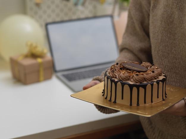 Zamknij widok kobiety w swetrze trzymając tort urodzinowy w dłoniach