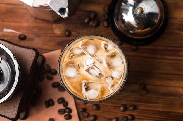 Zamknij widok kostek lodu w zimnej kawie parzonej w szkle na ciemnej powierzchni