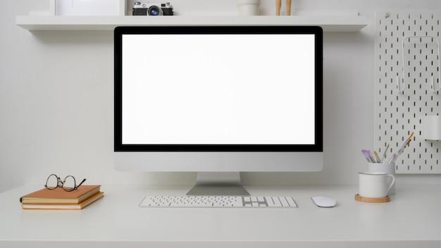 Zamknij widok l obszaru roboczego z komputerem z pustym ekranem, materiałami biurowymi i dekoracjami