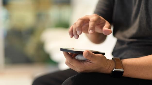 Zamknij widok mężczyzny korzystającego ze smartfona siedzącego w rozmytym tle