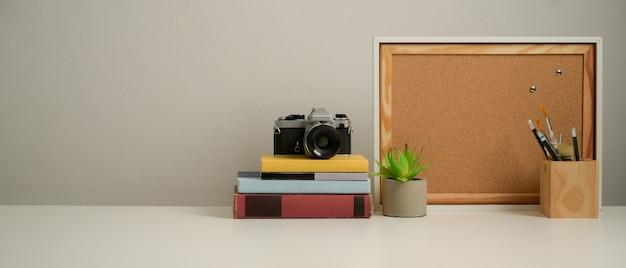 Zamknij widok miejsca pracy z miejscem na kopię, książki, aparat, artykuły papiernicze i dekoracje na białym stole w biurze domowym
