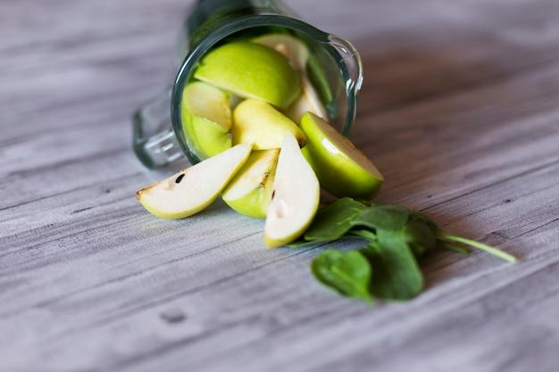 Zamknij widok miksera dzbanek z zielonymi naturalnymi składnikami: jabłkiem, szpinakiem i gruszką. stół szary tło. w domu, w ciągu dnia i stylu życia