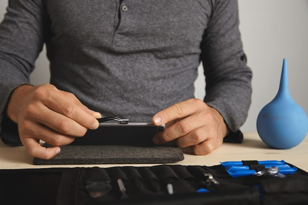 Zamknij widok, mistrz używa narzędzia pincher, aby wyjąć gniazdo karty sim ze smartfona podczas jego demontażu