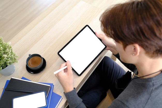 Zamknij widok młodego człowieka siedzącego na drewnianej podłodze i trzymając tablet cyfrowy z pustym ekranem.
