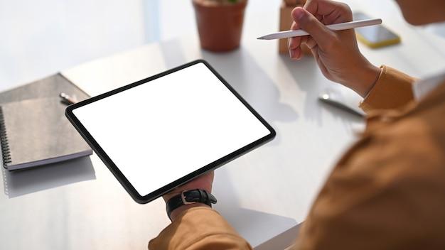Zamknij widok młodego człowieka trzymającego poziomy cyfrowy tablet z pustego ekranu przy białym biurku.
