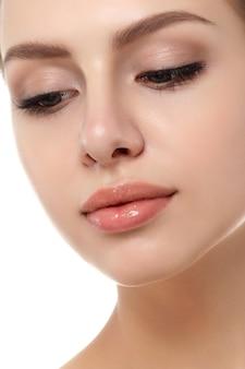 Zamknij widok młodej pięknej kobiety rasy kaukaskiej na białym tle. konturowanie ust, pielęgnacja skóry, koncepcja kosmetologii
