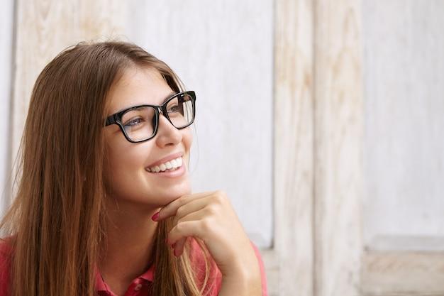 Zamknij widok młodej szczęśliwej pięknej kobiety z luźnymi włosami w stylowych okularach i patrzącej przed siebie z zamyślonym i natchnionym uśmiechem, dotykając jej brody, marząc o czymś