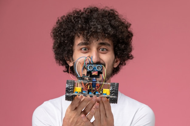 Zamknij widok młody człowiek uśmiecha się i wpatruje się w elektroniczne innowacje