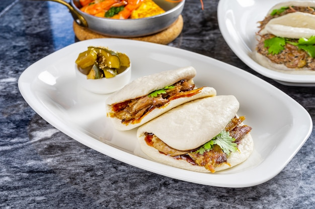 Zamknij widok na bao z filetem z kaczki. gua bao, bułeczki na parze podawane na białym talerzu. tradycyjne tajwańskie jedzenie gua bao na marmurowym stole. azjatycka kanapka gotowana na parze. azjatyckie fast foody. mięso