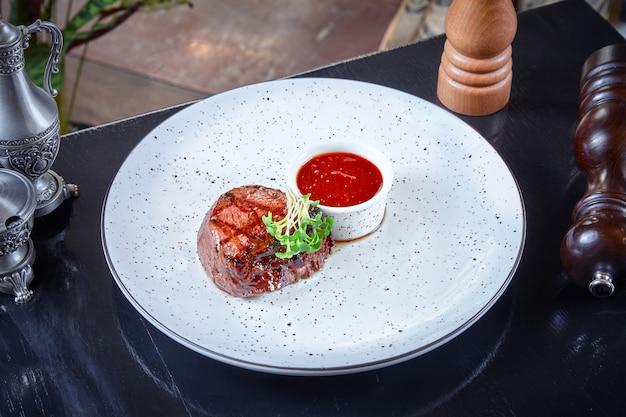 Zamknij widok na małej porcji steku wołowego gotowanego na grillu, podawany z czerwonym sosem na białym talerzu. amerykańskie jedzenie na lunch lub kolację. poziome tło żywności. skopiuj miejsce