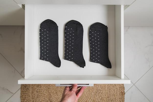 Zamknij widok na otwieranie szuflady męskiej dłoni z trzema takimi samymi szarymi męskimi skarpetkami minimalizm lub koncepcja życia kawalerskiego