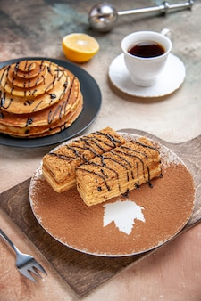 Zamknij widok na pyszne desery i filiżankę herbaty, cytryny i cynamonu na kolorowym stole