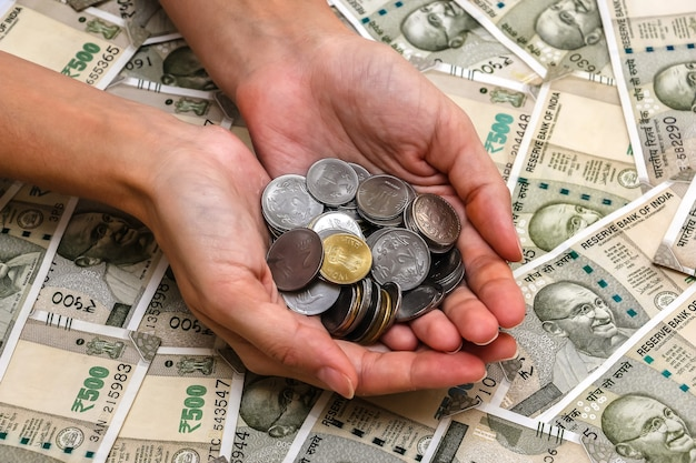 Zamknij widok na ręce kobiety z monet rupii indyjskich. 500 banknotów rupii w tle.