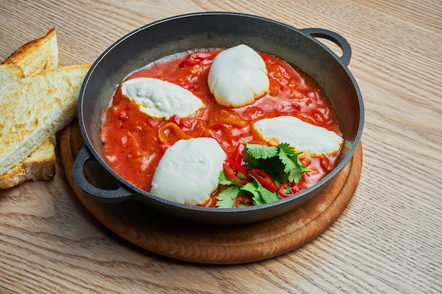 Zamknij widok na shakshuka z ostrą papryczką chili w soku pomidorowym z dodatkiem ciecierzycy, sera i papryki. tradycyjna kuchnia izraelska