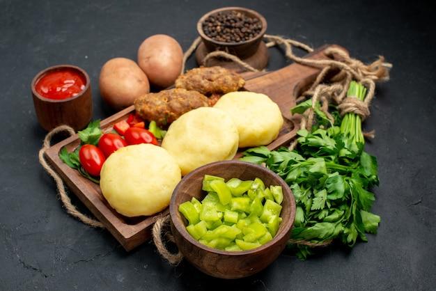 Zamknij widok na smaczne kotlety posiekane warzywa i keczup na kolację w ciemności