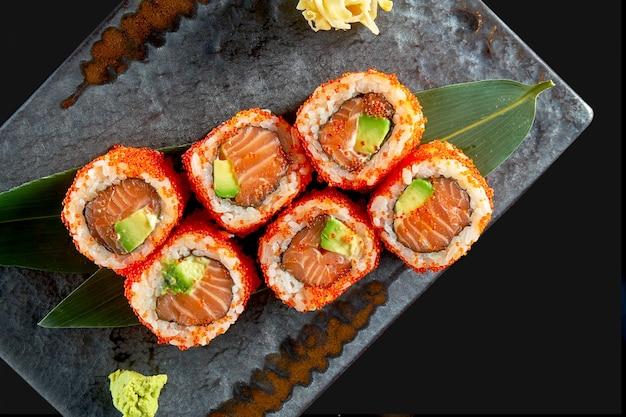 Zamknij widok na smaczne uramaki z łososiem, awokado i kawiorem tobiko. japońska kuchnia tradycyjna. dostawa jedzenia. pojedynczo na czarno