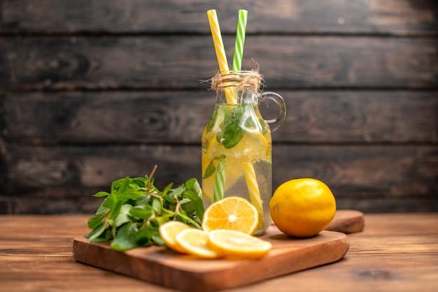 Zamknij widok naturalnej świeżej wody detoksykującej podawanej z miętą w tubce i pomarańczą na brązowym tle