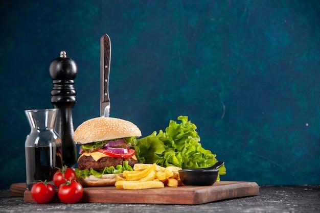 Zamknij widok noża w kanapce z mięsem i frytkami pomidorami z łodygą zielony pakiet na drewnianej desce keczup sos na ciemnoniebieskiej powierzchni