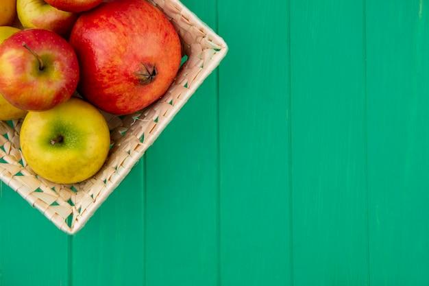 Zamknij widok owoców jak granat i jabłka w koszu na zielonej powierzchni