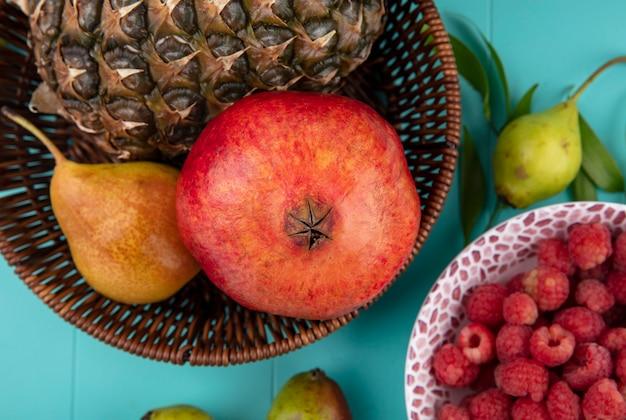 Zamknij widok owoców jako brzoskwini granatu ananasa w koszu i miski malin z brzoskwiniami i liśćmi na niebieskiej powierzchni