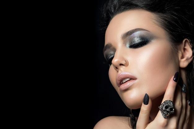 Zamknij widok pięknej kobiety z doskonałej skóry i makijaż wieczorowy dotykając jej twarzy
