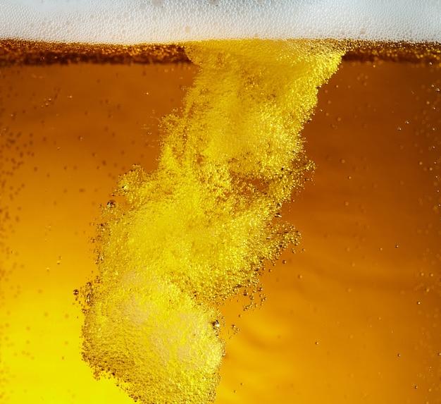 Zamknij widok pływających bąbelków w lekkiej teksturze piwa