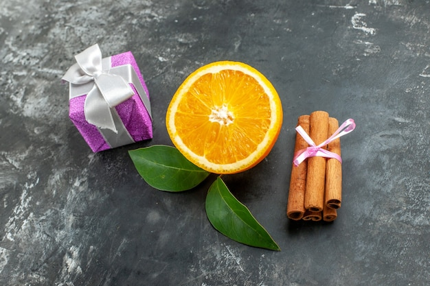 Zamknij widok pokrojonej świeżej pomarańczy w pobliżu prezentu i limonek cynamonowych na ciemnym tle