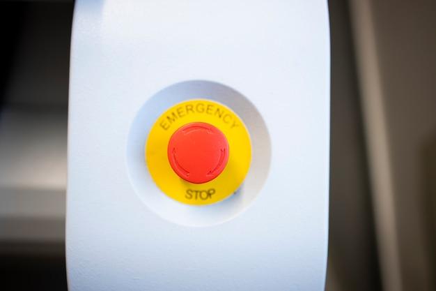 Zamknij widok przycisku zatrzymania awaryjnego maszyny przemysłowej.