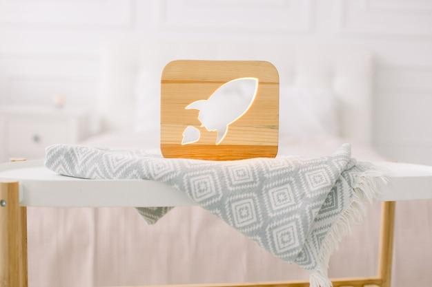Zamknij widok przytulnej drewnianej lampki nocnej z wyciętym obrazem rakiety, na szarym kocu w przytulnym, jasnym wnętrzu sypialni