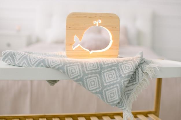 Zamknij widok przytulnej drewnianej lampki nocnej z wyciętym obrazem wieloryba, na szarym kocu w przytulnym jasnym wnętrzu sypialni.