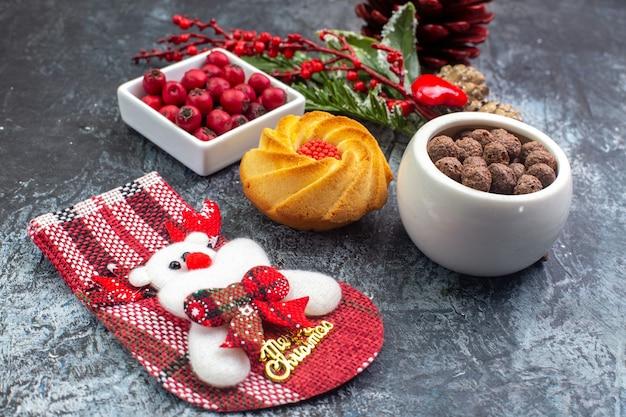 Zamknij widok pysznej dekoracji ciastek akcesoria skarpety świętego mikołaja i cornell w misce gałęzie jodły na ciemnej powierzchni