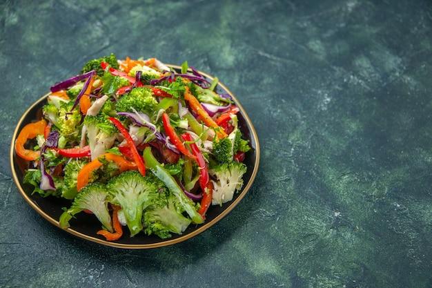 Zamknij widok pysznej wegańskiej sałatki na talerzu z różnymi świeżymi warzywami po prawej stronie na ciemnym tle