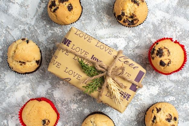 Zamknij widok pysznych małych babeczek z czekoladą wokół prezentu z napisem miłości na powierzchni lodu