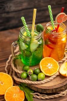 Zamknij widok pysznych świeżych soków i owoców na drewnianej tacy na brązowym tle