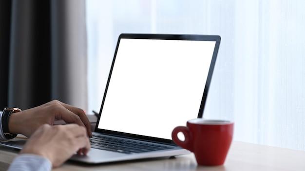 Zamknij widok rąk człowieka pracy na komputerze przenośnym w swoim miejscu pracy. pusty ekran dla tekstu reklamowego.
