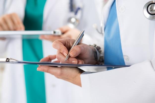 Zamknij widok rąk lekarza, robiąc notatki w schowku i tablecie