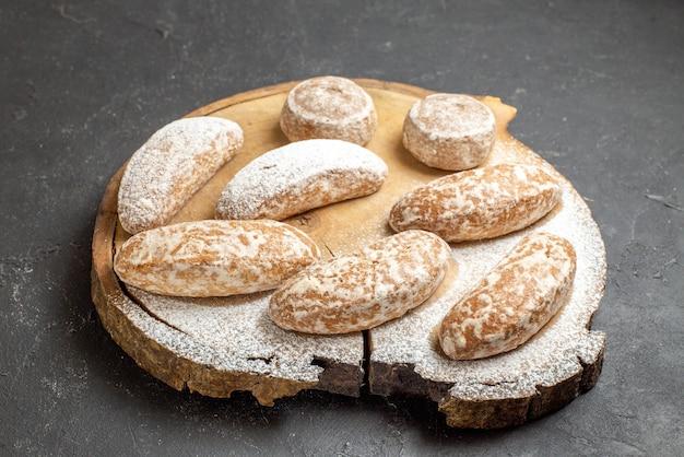 Zamknij widok różnych rodzajów pysznych ciasteczek na zepsutej desce do krojenia w ciemności