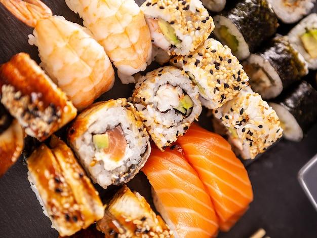 Zamknij widok różnych sushi na czarnym tle kamienia