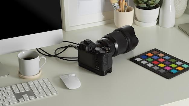 Zamknij widok stołu roboczego z aparatem, sprawdzaniem kolorów, urządzeniem komputerowym i dekoracjami