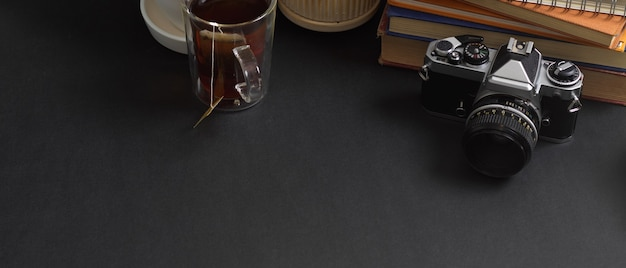 Zamknij widok stołu roboczego z miejscem na kopię, aparatem, książkami i filiżanką kawy w pokoju biurowym