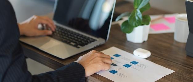 Zamknij widok strony biznesmen pracy z laptopem i dokumentacji na drewnianym stole