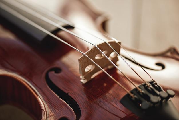 Zamknij widok strun piękne brązowe skrzypce leżące na drewnianym tle. instrumenty muzyczne. sprzęt muzyczny. muzyka w tle