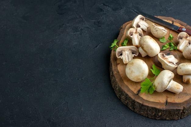 Zamknij widok surowych grzybów i zieleni nóż na drewnianej desce po lewej stronie na czarnym tle z wolną przestrzenią