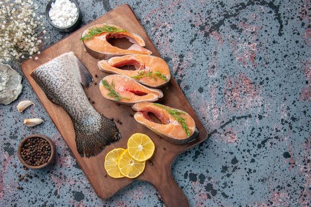 Zamknij widok surowych ryb plasterki cytryny zielonego pieprzu na drewnianej desce do krojenia i kwiat na niebiesko czarnych kolorach tabeli