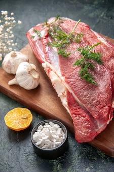 Zamknij widok świeżych surowych czerwonych mięs zielony czosnek nóż na brązowej drewnianej desce do krojenia sól kwiat cytryny na ciemnym tle